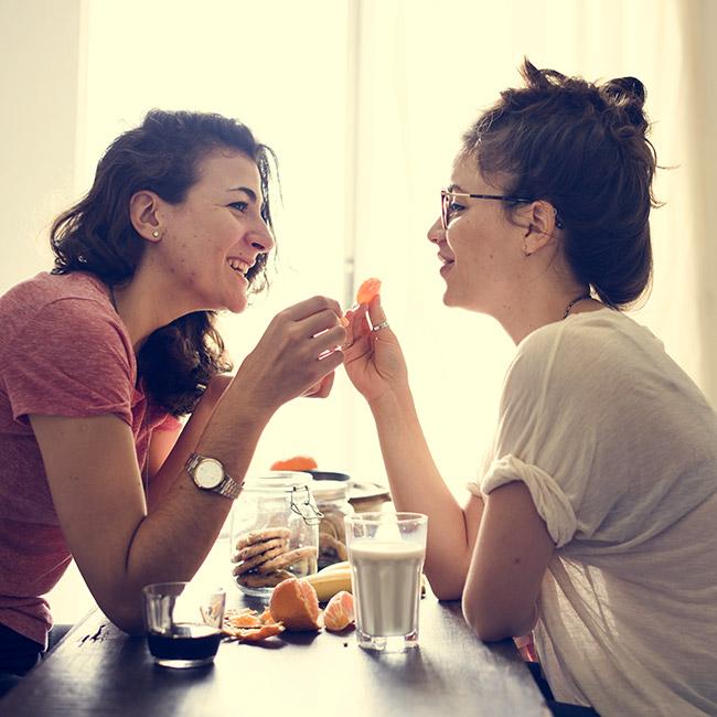 same sex couple living together having snack